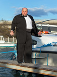 Fat man in tuxedo on deck boat