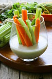carrots and celery with dip in a glass beakers