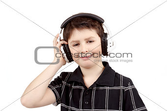 Portrait of a happy smiling young boy listening to music on headphones