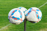 three football balls on holders