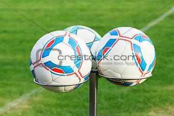 three football balls on holders