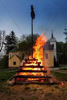 big night fire with witch on pile behind the church