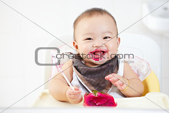 Baby eating dragon fruit