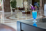 alcoholic cocktail of blue color is in the lobby of prestige hotel