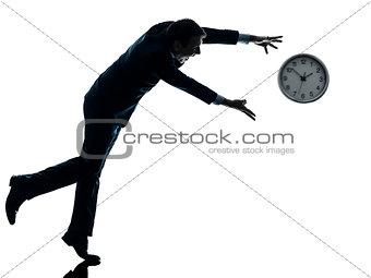 business man running after clock silhouette