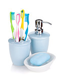 Four colorful toothbrushes and soap