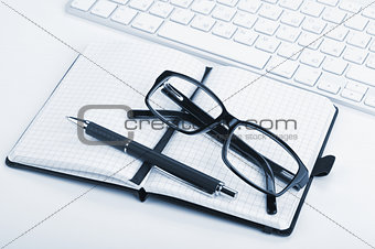 Office supplies, glasses and computed keyboard