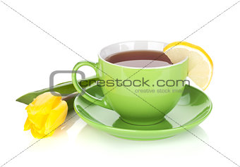 Green tea cup and yellow tulip