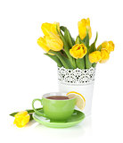 Yellow tulips and tea cup with lemon slice