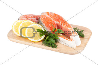 Salmon steaks on cutting board with lemons and herbs