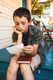 young boy reading letter on front porch