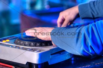 Dj mixes the track in the nightclub at a party
