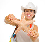 Closeup on starfish in hand of beach young woman