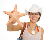 Smiling beach young woman showing starfish