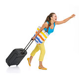 Full length portrait of young tourist woman with wheel bag catch