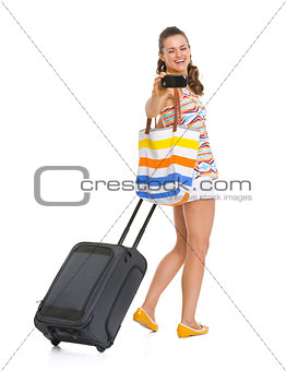 Happy young tourist woman with wheel bag taking photos with cell