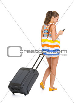 Young tourist woman with wheel bag writing sms . rear view