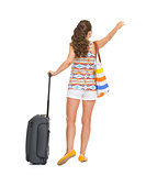 Full length portrait of tourist woman with wheel bag catching ta