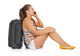 Young tourist woman with wheel bag sitting on floor and talking