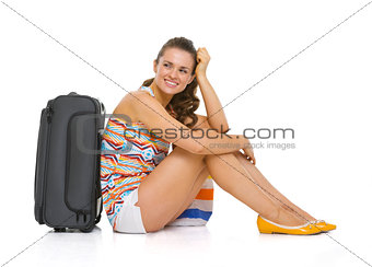 Young tourist woman with wheel bag sitting on floor and looking