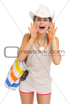Happy beach young woman shouting through megaphone shaped hands