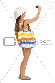 Full length portrait of beach young woman taking photo with came