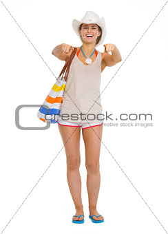 Full length portrait of happy beach young woman pointing in came