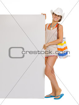 Full length portrait of happy beach young woman showing blank bi