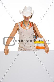Beach young woman showing blank billboard