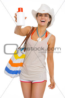 Happy beach young woman showing sun block creme
