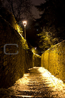 Old stone stairs with snow and lights at night