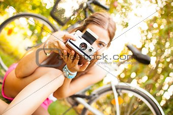 beautiful young woman playing with a vintage camera
