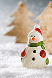 Christmas snowman in winter forest