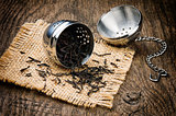 Metal tea infuser on wooden table