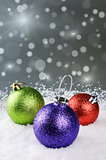 Colorful Christmas baubles on silver background