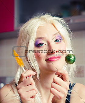 Portrait of smiling beautiful blonde girl with two candies in hands