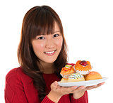 Asian woman holding a plate of cakes