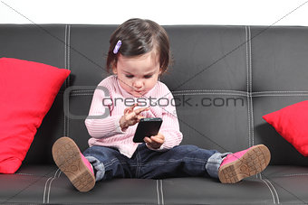 Casual baby sitting on a couch touching a mobile phone