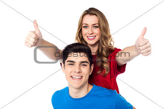 Joyous woman enjoying piggy ride and showing double thumbs up