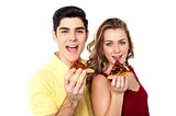 Couple posing with pizza slice, about to eat