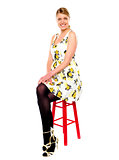 Glamourous woman sitting on stool