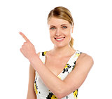 Happy young woman pointing copyspace