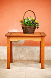 basket with flowers on wooden table
