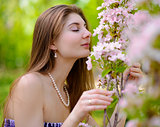 Young Beautiful Woman Smelling a Pink Sakura Flowers