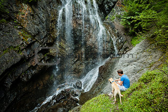 Young man with a dog near a waterfall