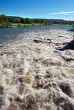 Brown River Rapids and Blue Sky