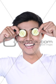 Asian Man with cucumber slices on eyes