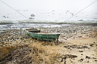 Old fishing boat at coast foggy in the morning