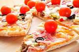 pizza with bacon, olives, cherry tomatoes, goat cheese, green pe