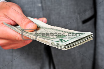 man in suit with a wad of dollars